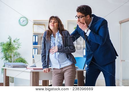 Pregnant woman struggling in the office and getting colleague he