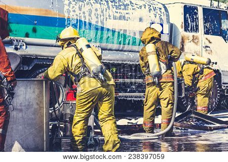 Firemen In Firefighter Uniform During Fire Drill And Training For Safety With Foam And Chemical Fire