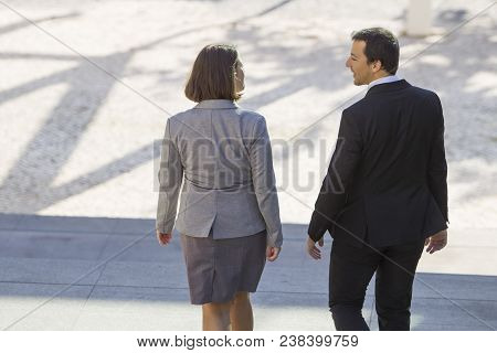 Rear View Of Business People In Formalwear Moving Down Stairs And Talking Outdoors. Modern Business