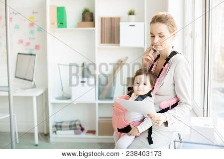 Young female agent with paper and smartphone working in office with her adorable baby daughter in carrier