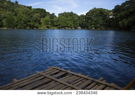 Rustic wooden raft on still water lake. Idyllic lake crossing with old raft. Summer travel to mountain camp. Fresh water lake view. Turquoise water. Wild nature ecotourism. Holiday camping by water poster