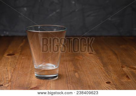 Empty Glass Glass Stands On A Wooden Table. Close Up View Of Empty Glass Standing On Wooden Table