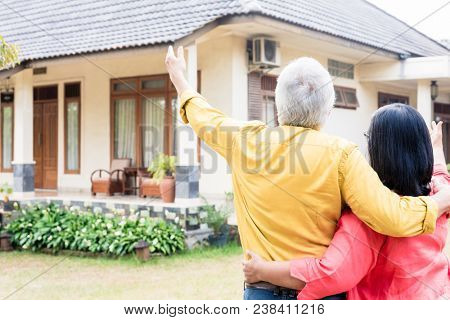 Elderly man pointing to a comfortable residential house while standing close to his wife