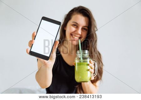 Young Pretty Woman Portrait Drink Smoothie And Show Shite Screen In Smartphone. White Background. Co