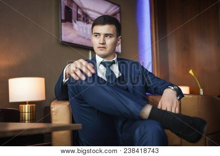 Young Asian Groom In Dark Blue Suit Sitting On A Leather Chair In The Room Of Hotel And Waiting For