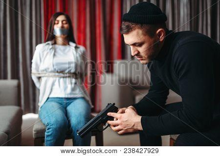 Killer sitting with gun against his female victim