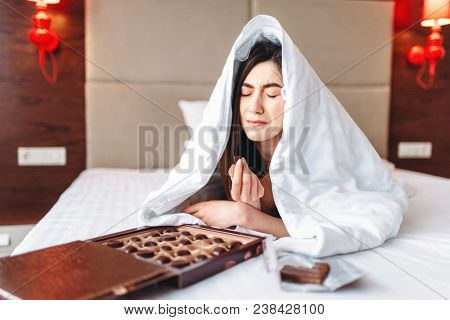 Woman lies under the blanket and eats sweets