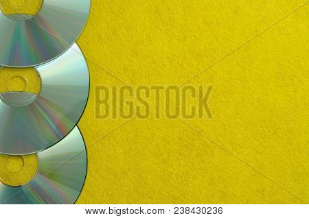 A Row Of Cd's On A Yellow Background