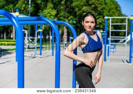 Strong Athletic Girl In A Bright Blue Sport Bra And Black Leggings On The Sport Playground. Photo Of