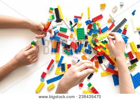 Vilnius, Lithuania - April, 2017. Children Hands Play With Colorful Lego Blocks On White Table.