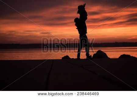 Young Father Lifting A Small Child Into The Air As They Stand Silhouetted Against A Colorful Vivid O