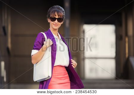 Young fashion business woman in sunglasses with handbag walking in city street Stylish female model wearing purple blazer and pink pencil skirt outdoors