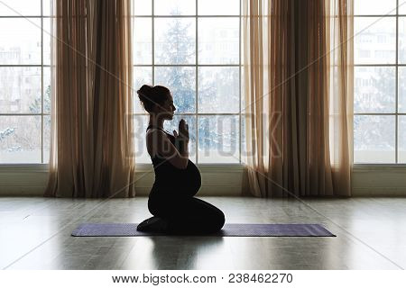Pregnant Woman Standing In Yoga Pose In Front Of Big Windows. Practicing Healthy Lifestyle While Pre