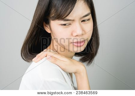 Asian Girl In White Casual Dress Catch That Shoulder, Because Of The Pain Of Hard Work. Or Something