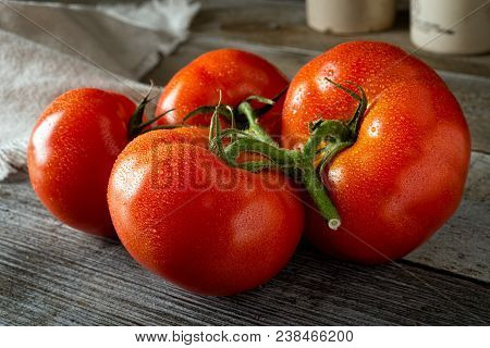 A Group Of Fresh Ripe Organic Tomatoes On A Rustic Farm Harvest Table.