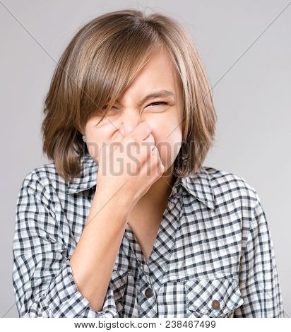 Portrait Attractive Caucasian Girl Making Bad Smell Sign. Beautiful Human Face Expression And Emotio