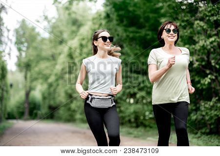 Young And Elder Woman In Sportswear Running In The Park During The Morning Exercise