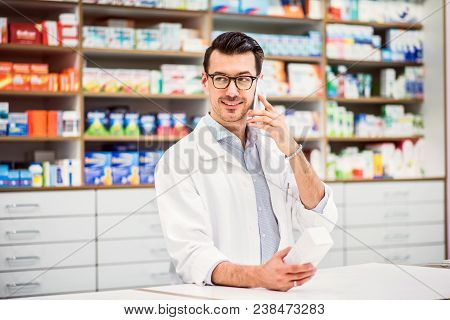Portrait Of A Young Atrractive Friendly Male Pharmacist With A Smartphone. Man Making A Phone Call.
