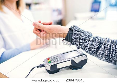 An Unrecognizable Customer Making Wireless Or Contactless Payment Using Smartwatch. Pharmacist Accep