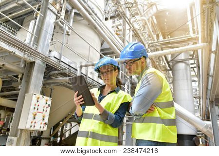 Industrial engineers working in recycling plant with tablet