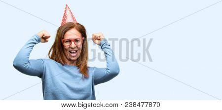 Middle age woman celebrates birthday happy and excited celebrating victory expressing big success, power, energy and positive emotions. Celebrates new job joyful isolated blue background