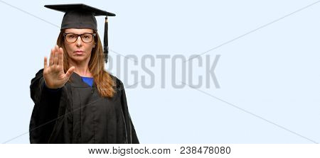 Senior graduate student woman annoyed with bad attitude making stop sign with hand, saying no, expressing security, defense or restriction, maybe pushing isolated blue background