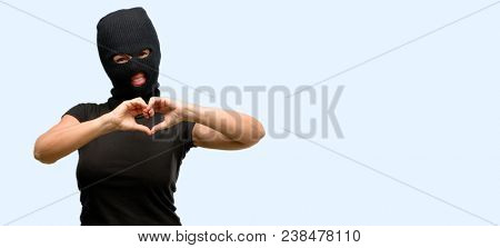 Burglar terrorist woman wearing balaclava ski mask happy showing love with hands in heart shape expressing healthy and marriage symbol isolated blue background