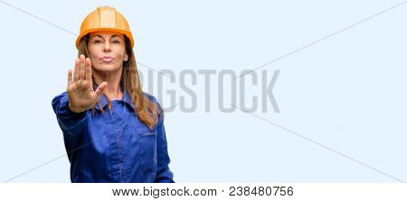 Engineer construction worker woman annoyed with bad attitude making stop sign with hand, saying no, expressing security, defense or restriction, maybe pushing isolated blue background