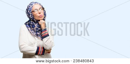 Middle age muslim arab woman wearing hijab thinking and looking up expressing doubt and wonder isolated blue background