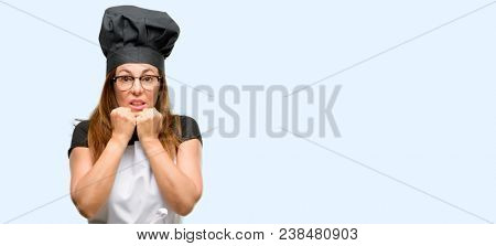 Middle age cook woman wearing chef apron terrified and nervous expressing anxiety and panic gesture, overwhelmed isolated blue background