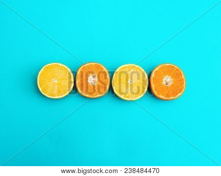 Citrus Fruit Flat Lay Two Halves Of Lemon And Two Halves Of Mandarin Are Lying On Bright Blue Backgr