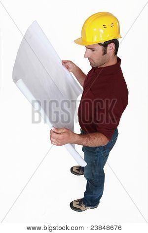 Tradesman examining a technical drawing