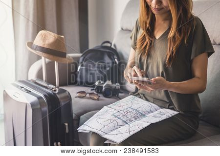 Young Woman Traveler Using Smart Phone And Looking Map For Planning Trip On Vacation, Travel Concept