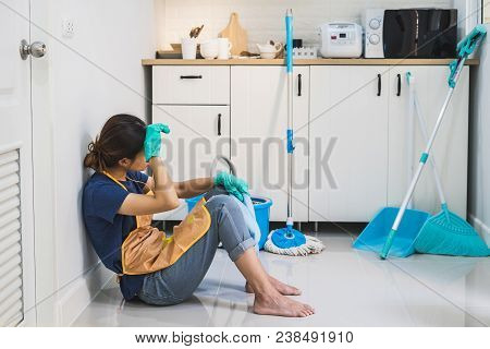 Tired Young Woman Sitting On Kitchen Floor With Cleaning Products And Equipment, Housework Concept
