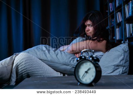 Portrait of dissatisfied girl with insomnia sitting on bed next to alarm clock at night