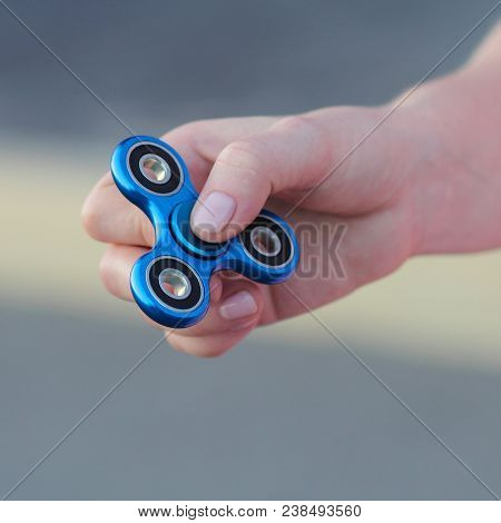 Girl In Pink T-shirt Is Playing Blue Metal Spinner In Hands On The Street, Woman Playing With A Popu