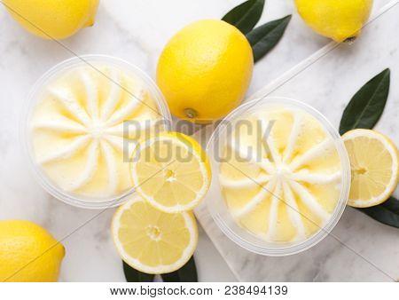 Plastic Jar With Lemon Cheesecake Mousse Dessert With Raw Lemons On Light Marblebackground