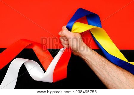 The man's hand clamps in the fist the symbols of the two flags on the background of the Right Sector flag. The conflict between Ukraine and Poland. poster
