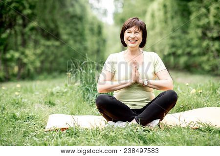 Elder Woman Meditating During The Yoga Exrecise In The Park