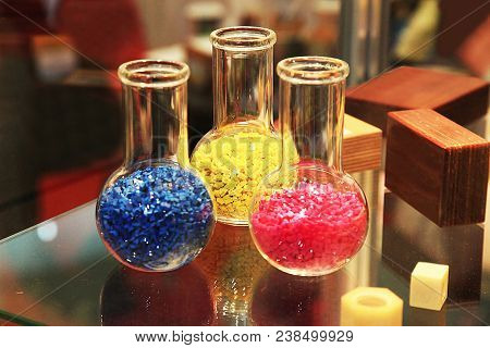 Colored Polymer Granules In Glass Flasks In Laboratory