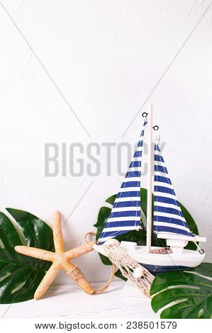 Decorative  Wooden Toy Boat, Sea Star And Tropical Plant Leaves  On White  Textured Background.  Pla