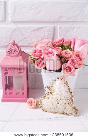 Pink Roses Flowers  In White Pot, Decorative Heart And Pink Lantern Against  White Brick Wall. Flora