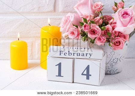 St. Valentine Day Background. Pink Roses Flowers, Calendar And  Yellow  Candles Against  White Brick