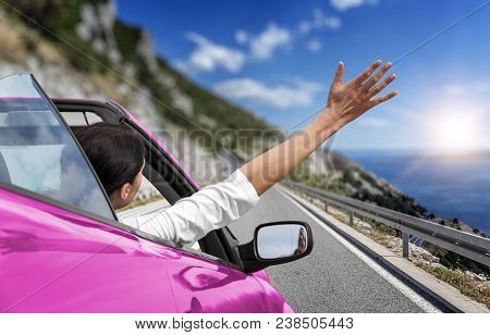 Young Woman Is Driving By Car To The Sea And Waving Her Hand From A Pink Convertible Car. Vacation O