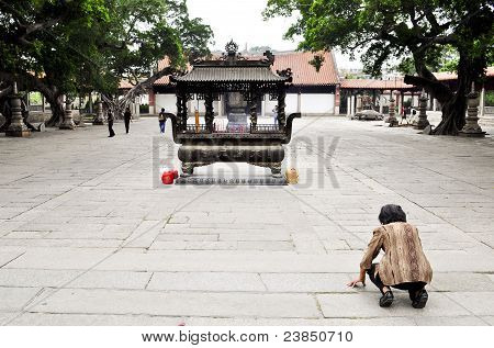 An Old Woman Prays To A Small Shrine