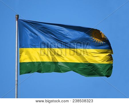 National Flag Of Rwanda On A Flagpole In Front Of Blue Sky.