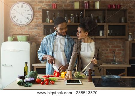 Happy African-american Couple Cooking Healthy Food And Having Fun Together In Their Loft Kitchen At