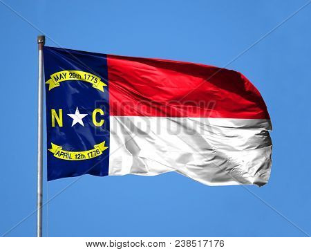 National Flag State Of North Carolina On A Flagpole In Front Of Blue Sky.