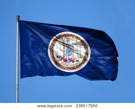 National Flag State Of Virginia On A Flagpole In Front Of Blue Sky.