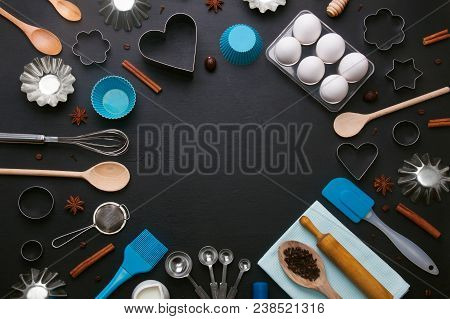 Baking Background With Eggs And Kitchen Tools: Rolling Pin, Wooden Spoons, Whisk, Sieve, Bakeware An